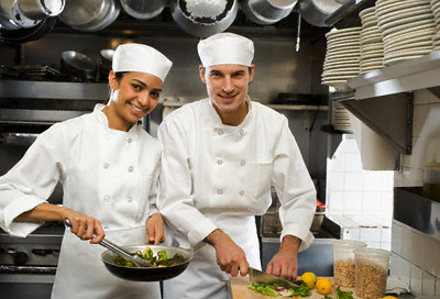 Male and female chefs in restaurant kitchen --- Image by © Royalty-Free/100965 - Corbis